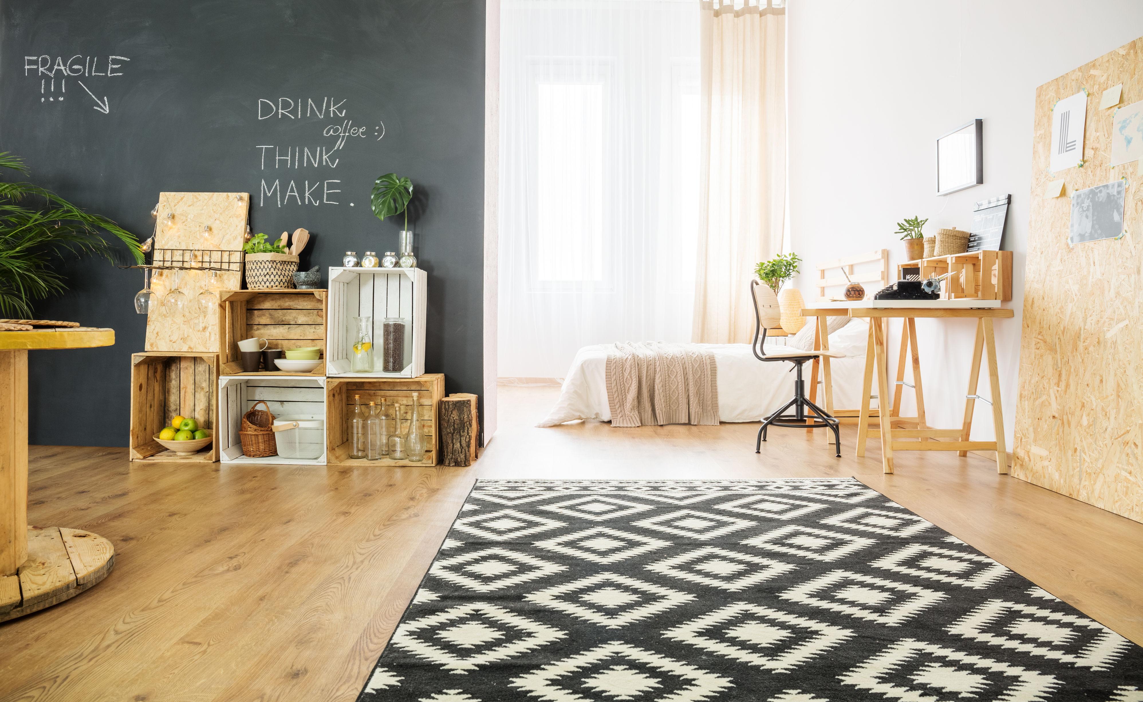 Spacieux studio avec lit double, caisses contre mur, tapis et bureau